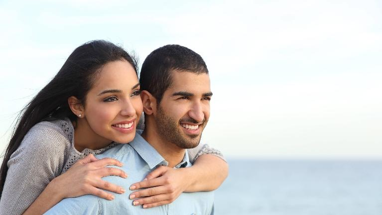young couple smiling at beach l dentist thornbury